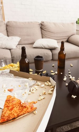 After party interior chaos. Beer bottles, popcorn and pizza on table in room